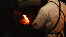 真っ赤に熱した鋼にハンマーを打ち下ろす